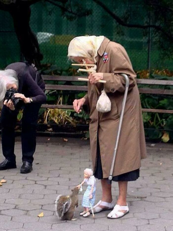 یک خانم پیر با عروسک پیرزنش در حال بازی با یک سنجاب!